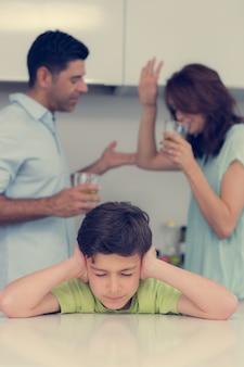 Triste joven cubriendo las orejas mientras los padres pelean en la cocina en casa