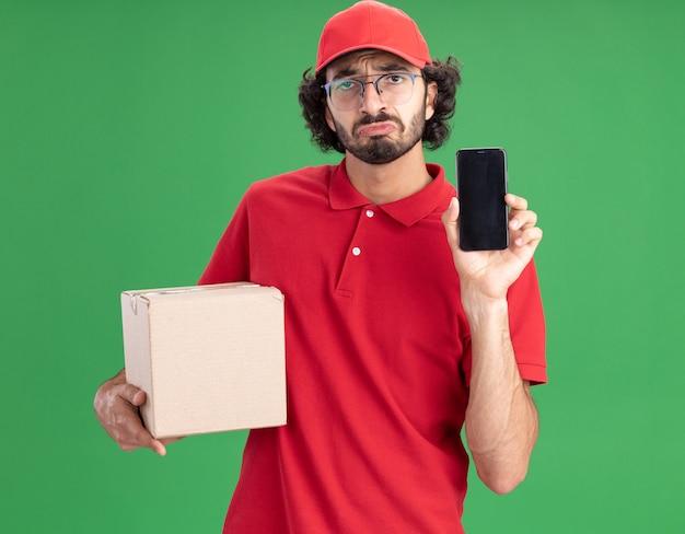 Triste joven repartidor caucásico en uniforme rojo y gorra con gafas sosteniendo cardbox mostrando teléfono móvil aislado en la pared verde