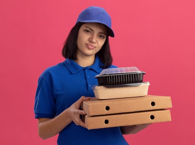 Triste joven repartidora en uniforme azul y gorra sosteniendo cajas de pizza y paquete de comida que parece estar disgustado de pie sobre la pared rosa
