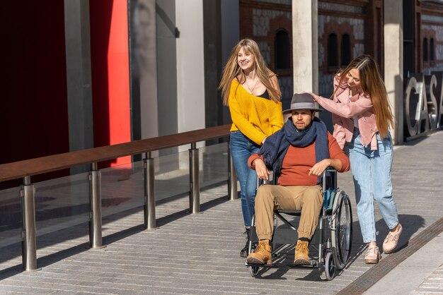 Triste joven en silla de ruedas con algunas chicas jóvenes que lo acompañan