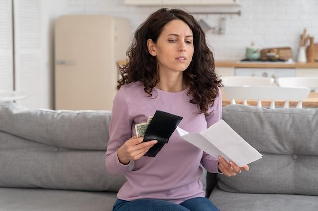 Triste joven sosteniendo el último dinero en efectivo sintiendo ansiedad por la deuda o la quiebra, sentada en casa.
