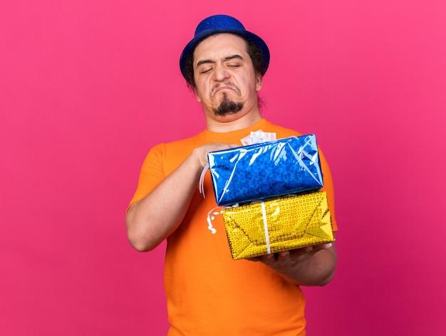 Triste joven vistiendo gorro de fiesta sosteniendo y mirando cajas de regalo