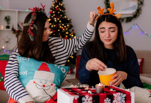 Triste jovencita con diadema de renos come palomitas de maíz sentada en un sillón con su amiga navidad en casa