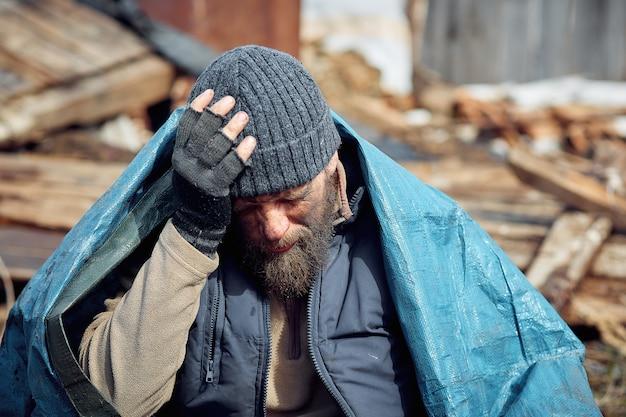Triste y molesto hombre sin hogar y desempleado en las ruinas