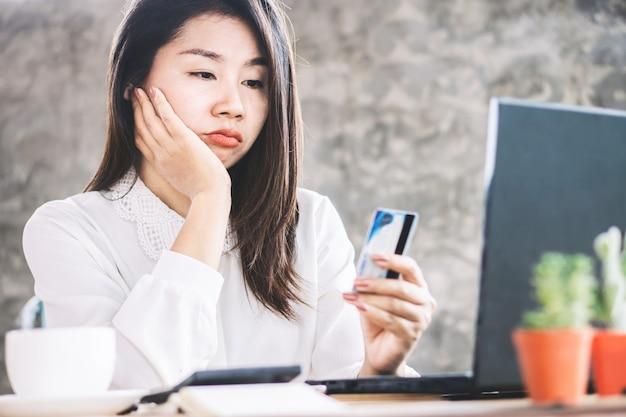 Triste mujer asiática sin dinero para tarjeta de crédito