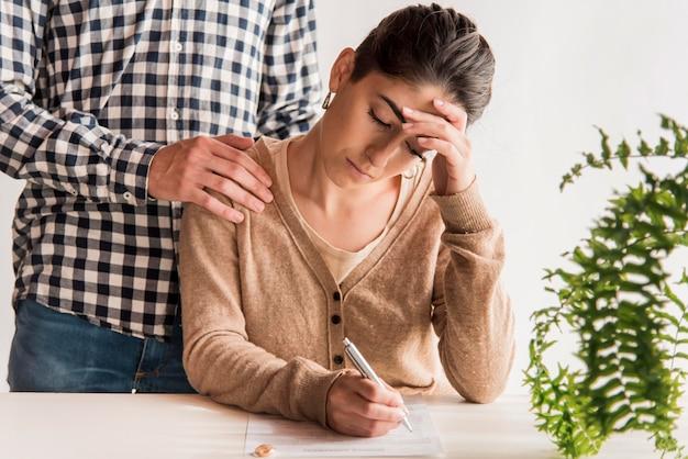 Triste mujer firma acuerdo de divorcio