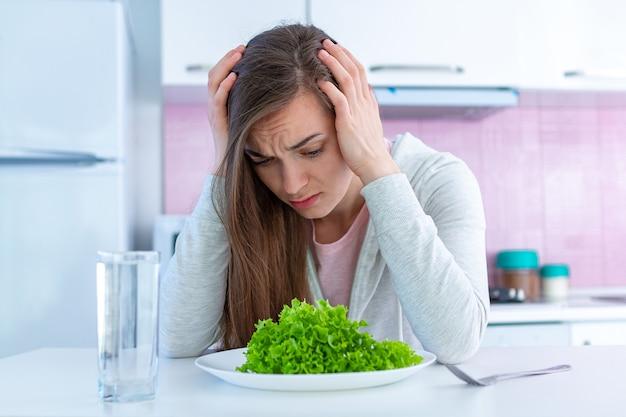 Triste mujer infeliz está cansada de hacer dieta y no querer comer alimentos orgánicos, limpios y saludables