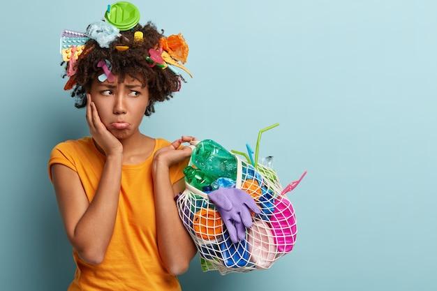 Triste mujer insatisfecha se abrocha el labio inferior, mira enojada a un lado, sostiene una bolsa de red con desechos plásticos, limpia el territorio, es ecológica, enojada con las personas que contaminan el medio ambiente, usa una camiseta naranja
