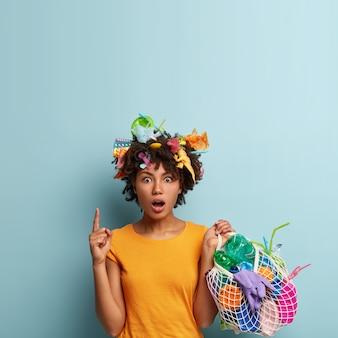 Triste mujer insatisfecha se abrocha el labio inferior, mira enojada a un lado, sostiene una bolsa de red con desechos plásticos, limpia el territorio