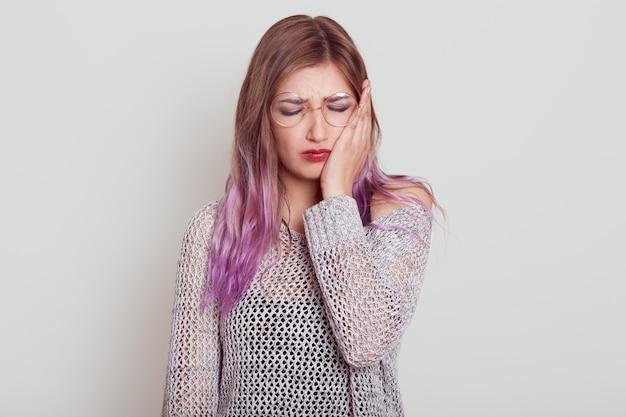 Triste mujer joven con cabello lila que sufre de un terrible dolor de muelas, tocándose la mejilla con la palma, mantiene los ojos cerrados, el ceño fruncido, aislado sobre fondo gris.