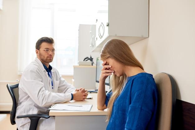Triste mujer joven en consultorio médico