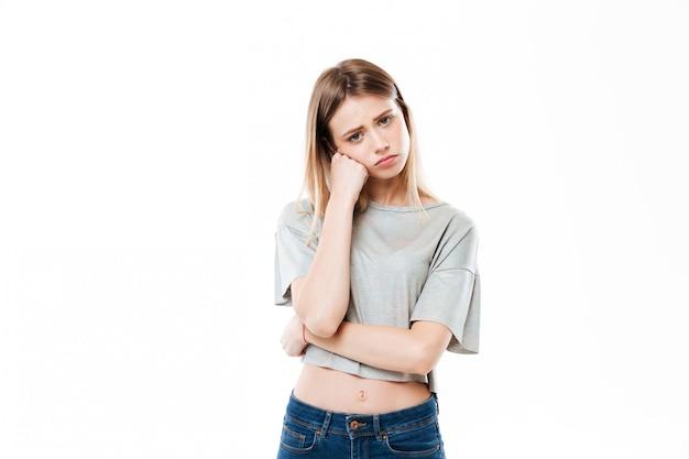 Triste mujer joven de pie aislado sobre pared blanca
