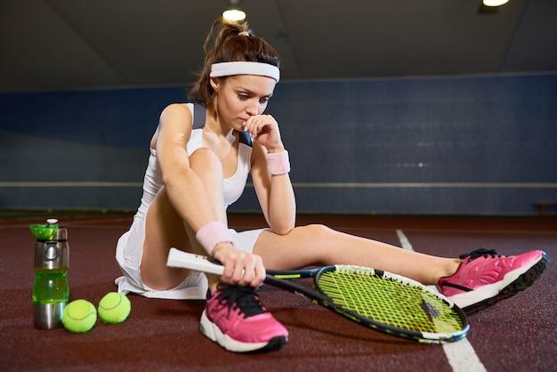 Triste mujer joven sentada en la cancha de tenis