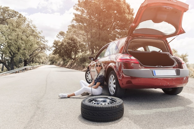 Triste mujer joven sentada cerca del coche averiado en la carretera recta