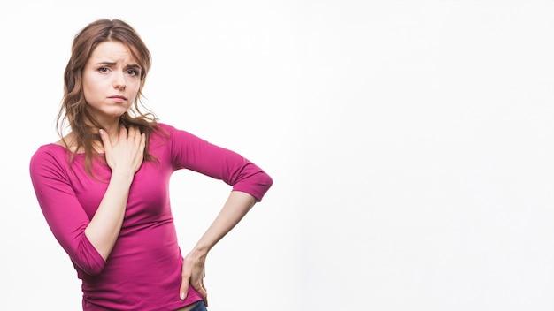 Triste mujer joven con su mano en las caderas contra el fondo blanco
