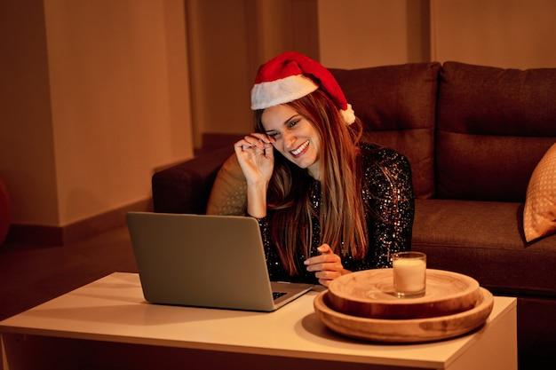 Triste mujer joven, vestida con un sombrero de santa claus haciendo una videollamada a su familia para celebrar la navidad. concepto de soledad, familia separada, distancia social y navidad.