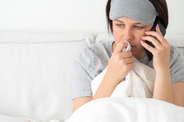 Triste mujer con máscara para dormir con teléfono inteligente mientras se sienta en la cama cubierta con edredón