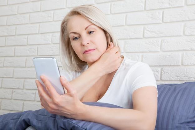 Triste mujer mayor sentada en la cama con teléfono inteligente.
