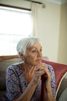 Triste mujer mayor sentada en el sofá en casa