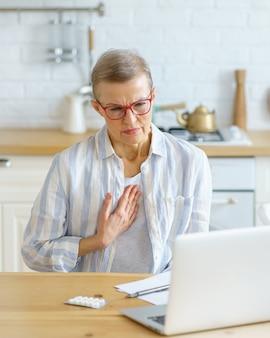 Triste mujer de mediana edad enferma que sufre de dolor en el pecho o tos con consulta en línea con