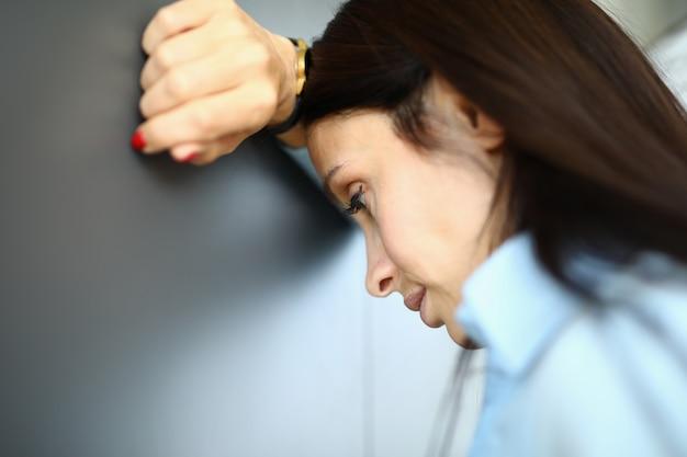 Triste mujer está de pie contra la pared con el codo en el brazo