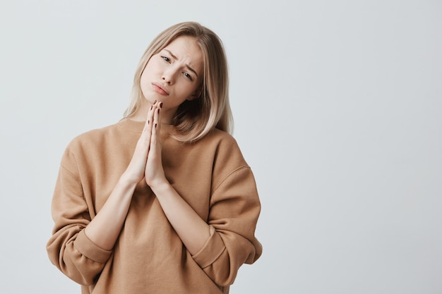 Triste mujer religiosa rubia hermosa tomados de la mano en oración con la esperanza de fortuna frunciendo el ceño. religión, concepto de espiritualidad.