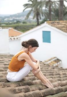 Triste mujer sentada en la cima de un techo, pensando en sus problemas