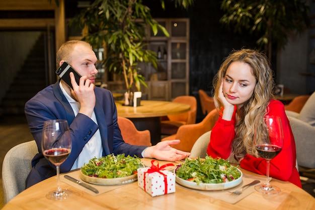 Triste mujer sentada a la mesa en el restaurante