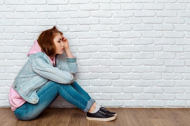 Triste mujer sentada en el piso cerca de la pared