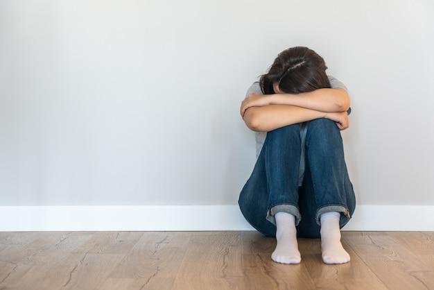 Triste mujer sentada en un piso solo en una habitación vacía, desesperación y concepto solitario con espacio de copia