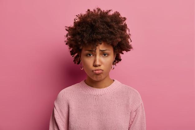 Triste mujer sombría hace pucheros labios, mira con expresión triste