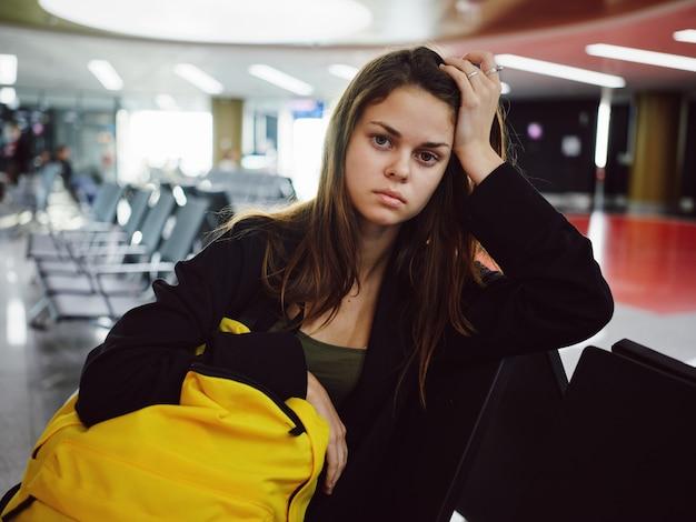 Triste mujer sosteniendo la mano en la cabeza espera del aeropuerto de mochila amarilla
