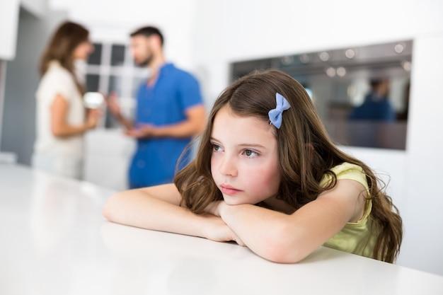 Triste niña apoyada en la mesa contra los padres discutiendo