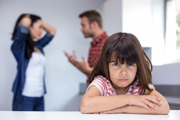 Triste niña escuchando a sus padres discutiendo
