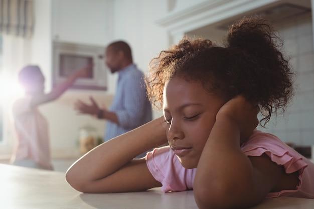 Triste niña harta de sus padres discutiendo en la cocina