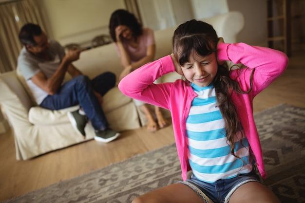 Triste niña harta de sus padres discutiendo