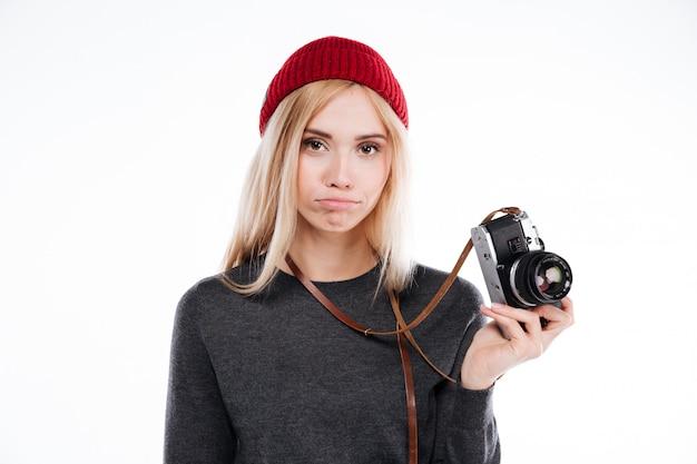 Triste niña molesta con sombrero de pie y sosteniendo la cámara retro
