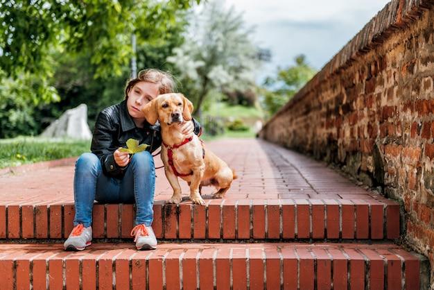 Triste niña con el perro sentado en las escaleras