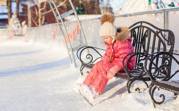 Triste niña sentada en un banco en la pista de patinaje