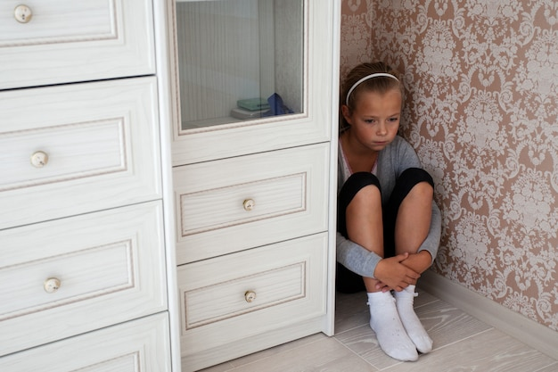 Triste niña sentada en la esquina de una habitación