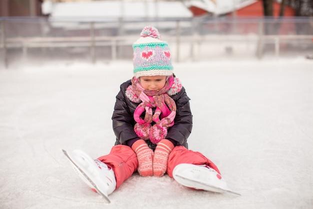 Triste niña sentada en una pista de patinaje después de la caída