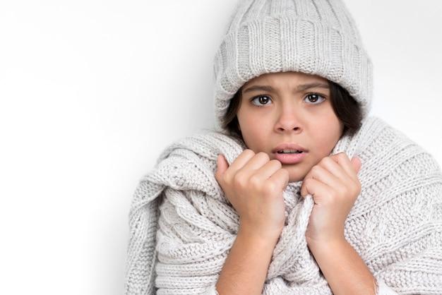 Triste niña con sombrero grueso y bufanda gris