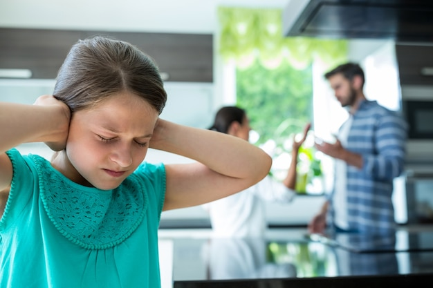 Triste niña tapándose los oídos mientras los padres discutían