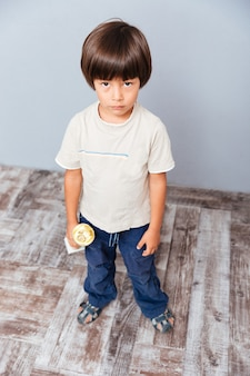 Triste niño lindo de pie y sosteniendo el trofeo de la taza