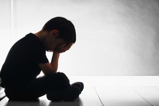 Triste niño sentado en el piso