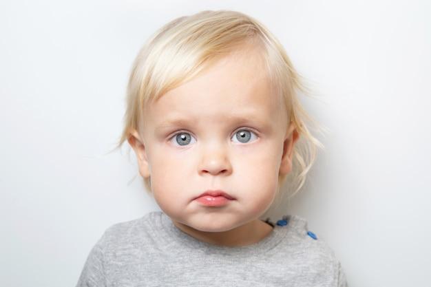 Triste o tímido bebé caucásico en una camiseta gris sobre blanco