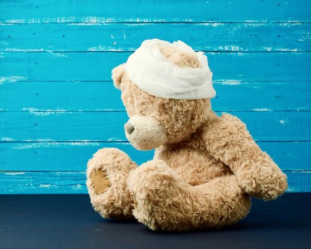 Triste oso pardo se sienta con cabeza de vendaje médico blanco vendado