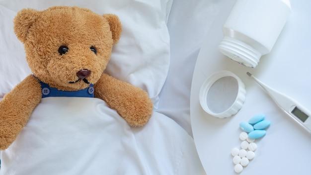 Triste oso de peluche tenía dolor de cabeza y fiebre, yacía enfermo en la cama
