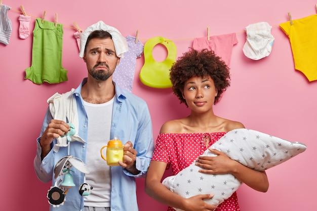 Triste padre cansado posa cerca de esposa pensativa con bebé en manos cuida del recién nacido cansado de pose de paternidad