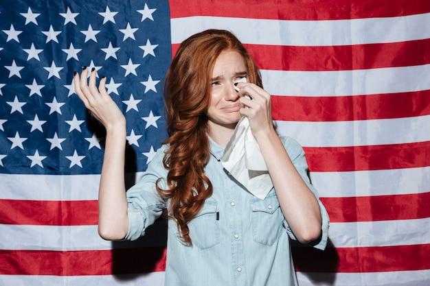 Triste pelirroja joven llorar sobre la bandera de estados unidos. mirando a un lado